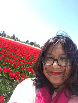 Moushumi taking a selfie in front of a field of red tulips